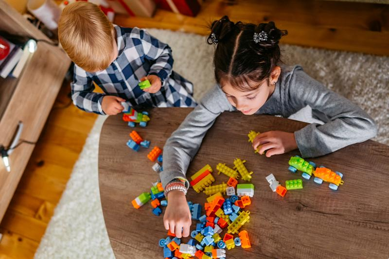 Two cute girls playing with train block toys at Christmas.