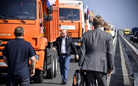 Russian President Vladimir Putin walks away from a construction truck after driving the vehicle across the new bridge - Credit: Alexander Nemenov/AFP