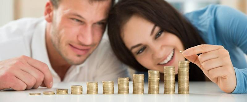 young couple counting their coins on a countertop