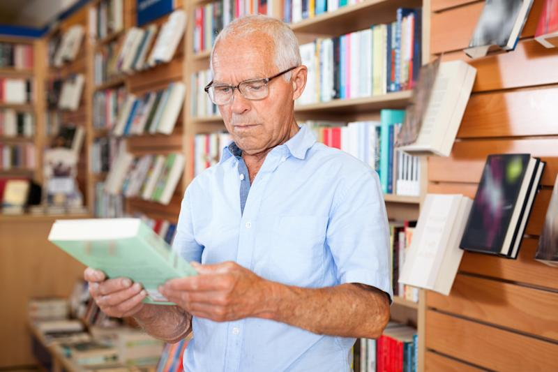 Senior man in bookstore holding book