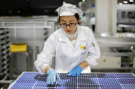 An employee works at a solar panel and solar equipment factory in Jiujiang in central China's Jiangxi Province, Tuesday, Jan. 5, 2021. Chinese leaders are shifting focus from the coronavirus back to long-term goals of making China a technology leader at this year's highest-profile political event, the meeting of its ceremonial legislature, amid tension with Washington and Europe over trade, Hong Kong and human rights. (Chinatopix via AP)