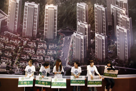 FILE PHOTO: Sales staff hold boards to promote a housing estate at a property trade fair in Dalian