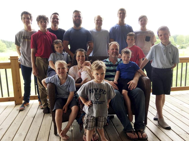 In a photo from May 30, 2018, the Schwandt family poses for a photo at their farm in Lakeview, Mich. Standing from left are Tommy, Calvin, Drew, Tyler, Zach, Brandon, Gabe, Vinny and Wesley. Seated, starting at upper left are Charlie, Luke, mother Kateri holding Finley, father Jay with Tucker and Francisco in the foreground. The 14-boy family ranges in age from 2 months to 25 years. And no girls. (AP Photo/Mike Householder)