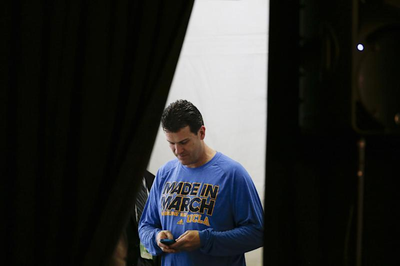 UCLA head coach Steve Alford enters text into his phone before a news conference during the NCAA men's college basketball tournament Saturday, March 22, 2014, in San Diego. UCLA faces Stephen F. Austin in a third-round game on Sunday. (AP Photo/Gregory Bull)