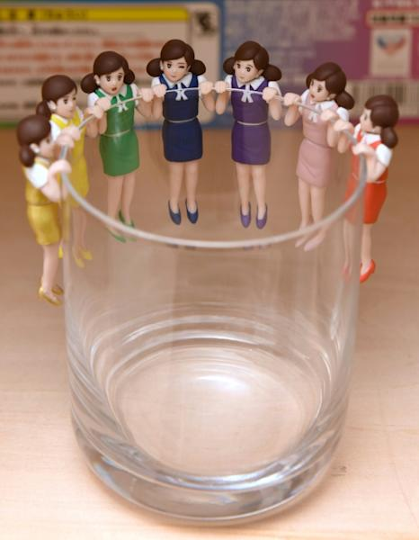 Tokyo-based manufacturer Kitan Club fueled the craze for capsule toys when it launched a special figurine of a woman wearing a typical office worker's clothes, whose arms or legs were designed to hang over the edge of a glass