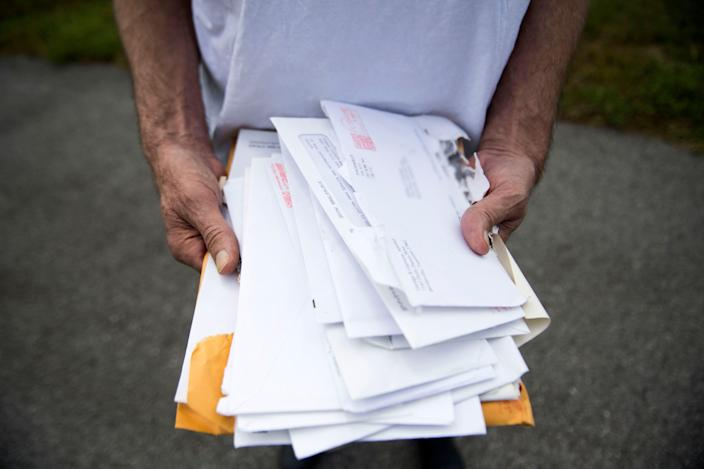 Alan Chrisman holds medical bills and records near the McDonald's where he worked at as a maintenance employee before being diagnosed with stage 4 colorectal cancer. This photo has been altered to blur the address on the envelope.