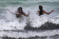 Women enjoy the waves from a high surf, Friday, July 31, 2020, in Miami Beach, Fla. Forecasters declared a hurricane warning for parts of the Florida coast Friday as Hurricane Isaias drenched the Bahamas on track for the U.S. East Coast. (AP Photo/Lynne Sladky)