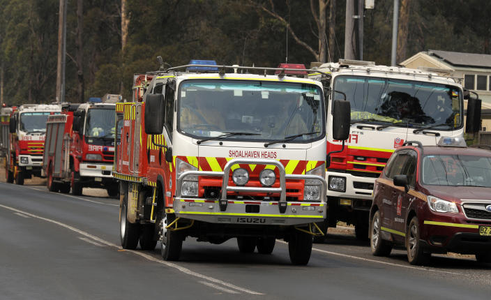 Firetrucks at staging area at Nowra, Australia, prepare to disperse to fires, Saturday, Jan. 4, 2020. Australia was bracing for one of the worst days in its wildfire crisis Saturday as strong winds and high temperatures were forecast to bring flames to more populated areas, including the suburbs of Sydney. (AP Photo/Rick Rycroft)