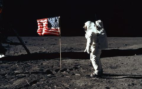 Aldrin poses beside the US flag, which was reinforced with metal so it appears to fly on the windless lunar surface  - Credit: NASA