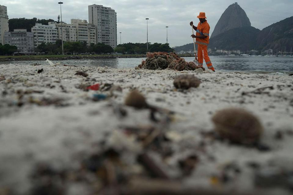 <p>A clean workers removes the trash over the sand of Botafogo beach next to the Sugar Loaf mountain and the Guanabara Bay in Rio de Janeiro, Brazil, Saturday, July 30, 2016. Just days ahead of the Olympic Games the waterways of Rio de Janeiro are as filthy as ever, contaminated with raw human sewage teeming with dangerous viruses and bacteria, according to a 16-month-long study commissioned by The Associated Press.(AP Photo/Leo Correa)</p>