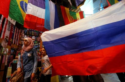 A picture taken on June 7, 2018 shows flags of countries participating in the 2018 FIFA World Cup on display among other flags outside a stall in the old city of the Syrian capital Damascus