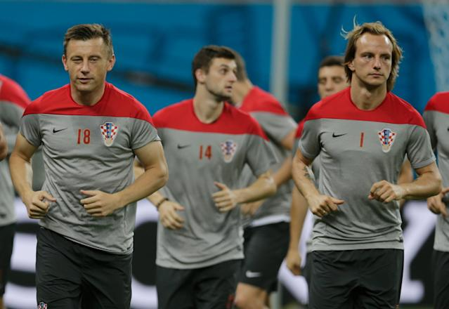 Croatia's Ivica Olic,left ,Marcelo Brozovic, center, and Ivan Rakitic warmup during an official training session the day before the group A World Cup soccer match between Cameroon and Croatia, at the Arena da Amazonia in Manaus, Brazil, Tuesday, June 17, 2014. (AP Photo/Fernando Llano)