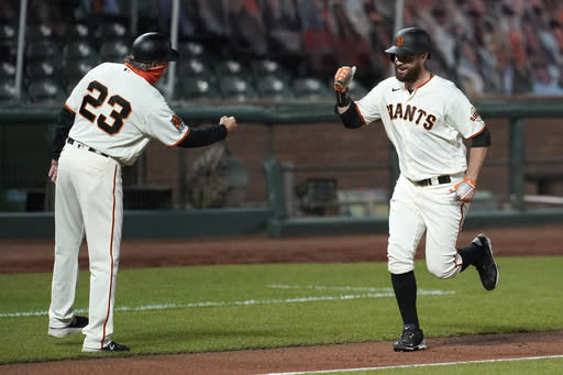 San Francisco Giants' Brandon Belt, right, is congratulated by third base coach Ron Wotus after hitting a two-run home run against the Seattle Mariners during the third inning of a baseball game in San Francisco, Wednesday, Sept. 16, 2020. This is a makeup of a postponed game from Tuesday in Seattle. (AP Photo/Jeff Chiu)