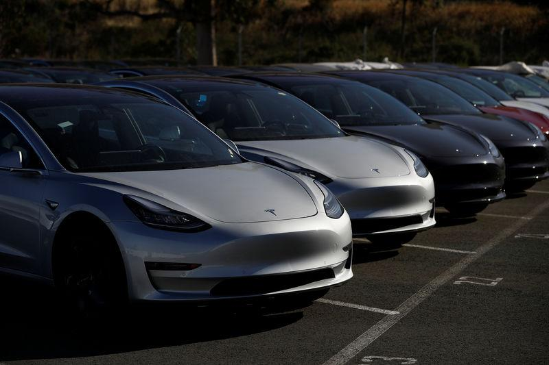 A row of new Tesla Model 3 electric vehicles is seen at a parking lot in Richmond, California