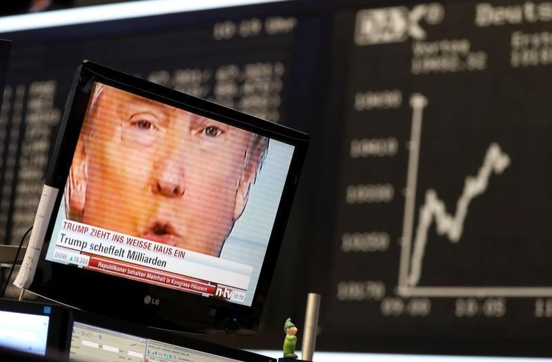 FILE PHOTO: A TV screen showing U.S. President-elect Trump is pictured in front of the German share price index DAX board in Frankfurt