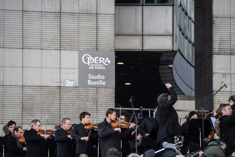 Paris Opera musicians set up on sunlit steps outside the Bastille Opera to play for several hundred passers-by