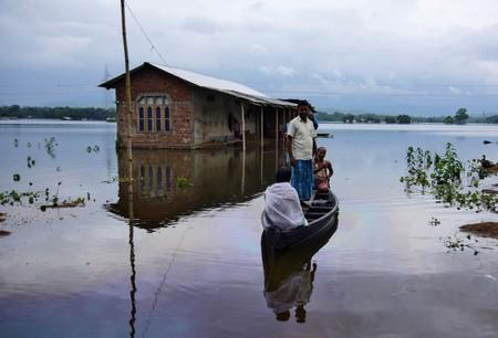 Villagers are transported on a boat towards a safer place at a flooded village in Nagaon district