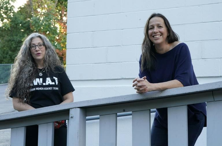 Shira Tarantino(L) and Brook Manewal of Suburban Women Against Trump (SWAT Team) pose as they campaign against the president's courting of female voters in the suburbs in Stamford, Connecticut on October 15, 2020