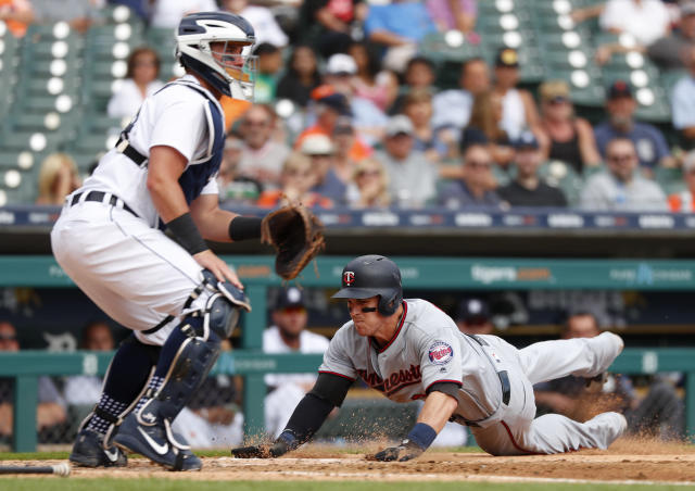 Minnesota Twins' Tyler Austin scores as Detroit Tigers catcher James McCann (34) waits for the throw in the fourth inning of a baseball game in Detroit, Wednesday, Sept. 19, 2018. (AP Photo/Paul Sancya)