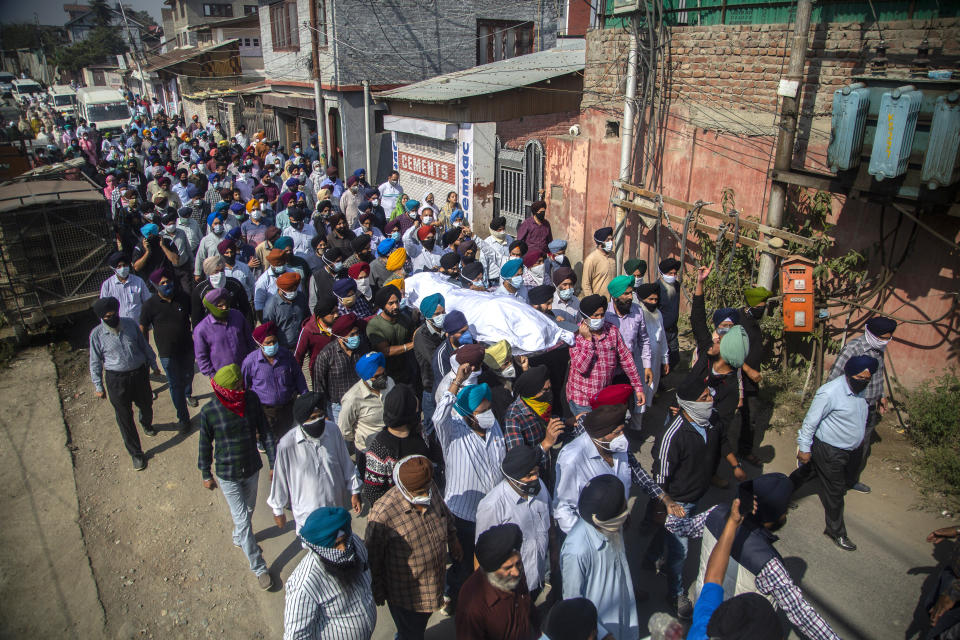 FILE-In this Oct. 8, 2021 file photo, Sikh community members carry the body of slain Satinder Kaur, a government school teacher during her funeral procession in Srinagar, India. Government forces have detained at least 500 people in a sweeping crackdown in Indian-controlled Kashmir, local officials said Sunday, following a string of suspected militant attacks and targeted killings in the disputed region. (AP Photo/Mukhtar Khan, File)