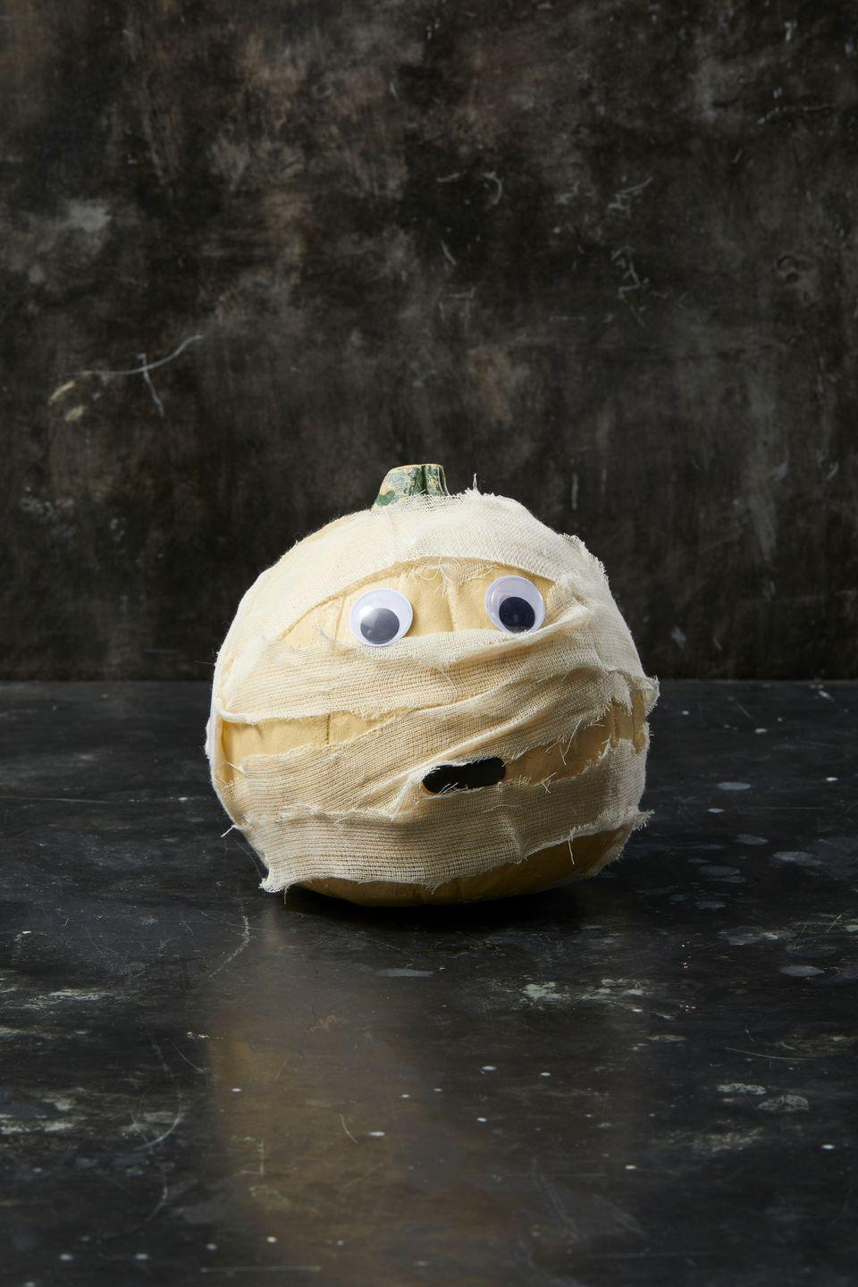 <p>To make this little guy, cut cheesecloth into 3-inch strips. Then put a dot of hot glue to start and wrap the pumpkin with the cheesecloth strips. Glue down the strips when you get to the end to ensure they stay in place. Once you are happy with the wrapping, attach two googley eyes to the face. Cut out a small mouth from paper and glue it under some of the cloth. </p>