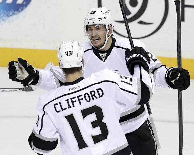 Los Angeles Kings defenseman Slava Voynov (26), of Russia, celebrates with Kyle Clifford (13) after Voynov scored against the Nashville Predators in the first period of an NHL hockey game Thursday, Oct. 17, 2013, in Nashville, Tenn. (AP Photo/Mark Humphrey)