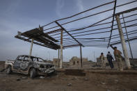 Yemeni fighters backed by the Saudi-led coalition look at damages in the aftermath of a ballistic missile and an explosive-laden drone fired by Yemen's Houthi rebels that hit a fuel station on June 5, 2021, killing two-year-old Liyan Taher and her father 32-year-old Taher Farag in the Rawdha neighborhood of the central city of Marib, Yemen, Sunday, June 20, 2021. (AP Photo/Nariman El-Mofty)