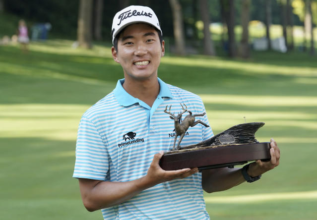FILE - In this July 15, 2018, file photo, Michael Kim holds the trophy after winning the John Deere Classic golf tournament in Silvis, Ill. Kim had missed six out of seven cuts and changed coaches when he showed up at the John Deere Classic last year. He broke the tournament record at 27-under 257 and won by eight shots, matching Dustin Johnson and Francesco Molinari for the largest victory margin of the season. And then it was as if the week never happened. (AP Photo/Charlie Neibergall, File)