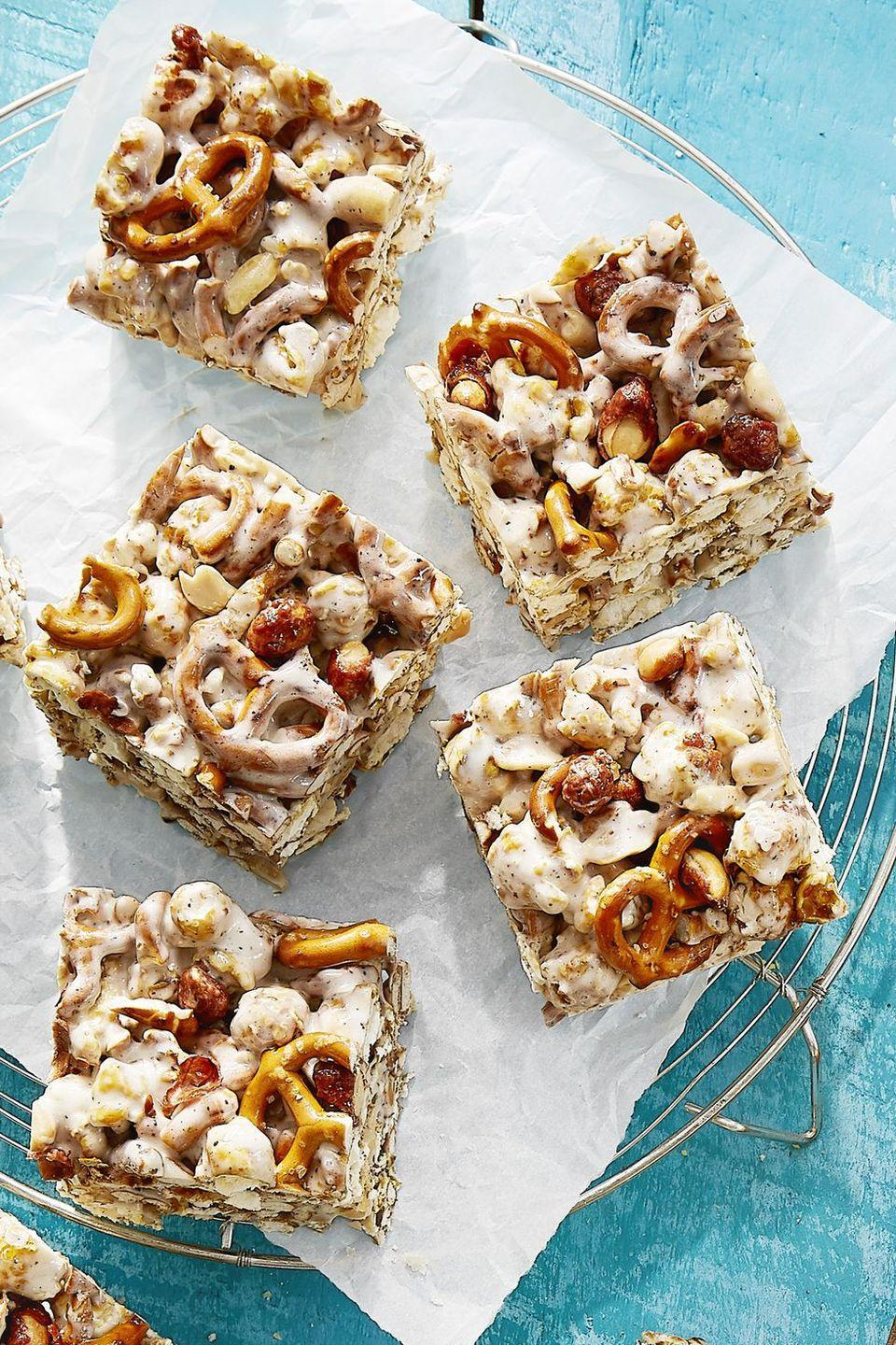 """<p>These ooey-gooey Game Day snacks are sure to please.</p><p><strong><a href=""""https://www.countryliving.com/food-drinks/recipes/a43071/cracker-jack-pretzel-treats-recipe/"""" rel=""""nofollow noopener"""" target=""""_blank"""" data-ylk=""""slk:Get the recipe"""" class=""""link rapid-noclick-resp"""">Get the recipe</a>.</strong></p><p><a class=""""link rapid-noclick-resp"""" href=""""https://www.amazon.com/USA-Pan-Bakeware-Rectangular-Aluminized/dp/B0029JOC6I/?tag=syn-yahoo-20&ascsubtag=%5Bartid%7C10050.g.5080%5Bsrc%7Cyahoo-us"""" rel=""""nofollow noopener"""" target=""""_blank"""" data-ylk=""""slk:SHOP BAKING PANS"""">SHOP BAKING PANS</a><br></p>"""