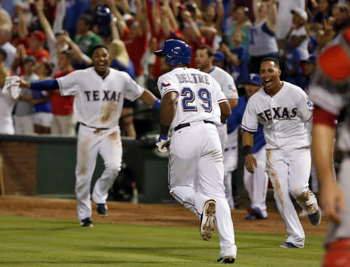 Texas Rangers' Adrian Beltre (29) heads up the first base line after hitting the game-winning home run as teammates Elvis Andrus, left, and Leonys Martin, right, run out of the dugout in celebration during the ninth inning of a baseball game against the Los Angeles Angels, Wednesday, July 31, 2013, in Arlington, Texas. The Rangers won 2-1. (AP Photo/Jim Cowsert)
