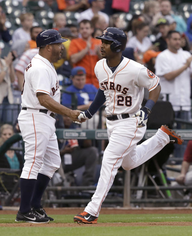 Houston Astros' L.J. Hoes (28) shakes hands with third base coach Pat Listach after hitting a two-run home run against the Texas Rangers in the second inning of a baseball game Tuesday, May 13, 2014, in Houston. (AP Photo)