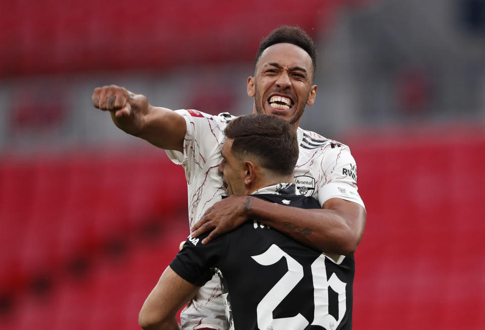 Arsenal's Pierre-Emerick Aubameyang, top, celebrates with Arsenal goalkeeper Emiliano Martinez after scores the winning penalty in a penalty shootout at the end of the English FA Community Shield soccer match between Arsenal and Liverpool at Wembley stadium in London, Saturday, Aug. 29, 2020. (Andrew Couldridge/Pool via AP)
