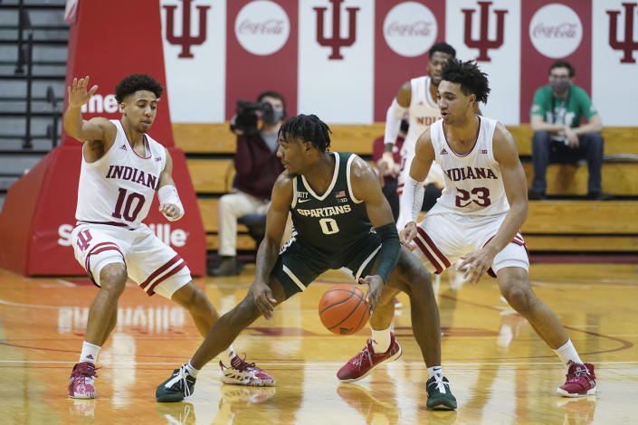 Michigan State's Aaron Henry (0) is defended by Indiana's Rob Phinisee (10) and Trayce Jackson-Davis (23) during the second half of an NCAA college basketball game, Saturday, Feb. 20, 2021, in Bloomington, Ind. Michigan State won 78-71. (AP Photo/Darron Cummings)