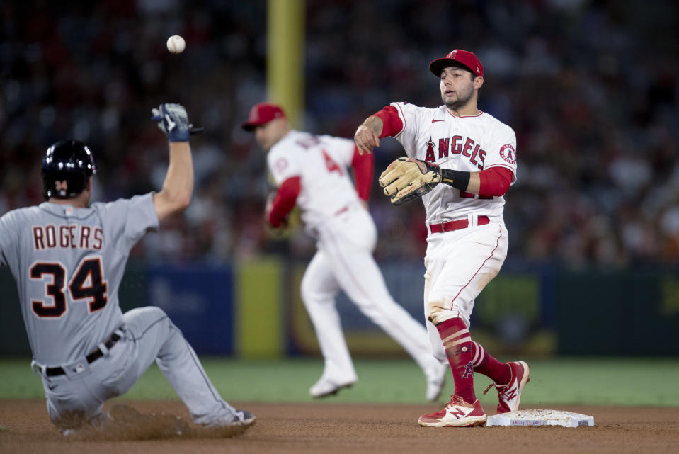 Los Angeles Angels second baseman David Fletcher, right, turns a double play over the slide by Detroit Tigers' Jake Rogers during the fifth inning of a baseball game in Anaheim, Calif., Saturday, June 19, 2021. Harold Castro was out at first. (AP Photo/Kyusung Gong)