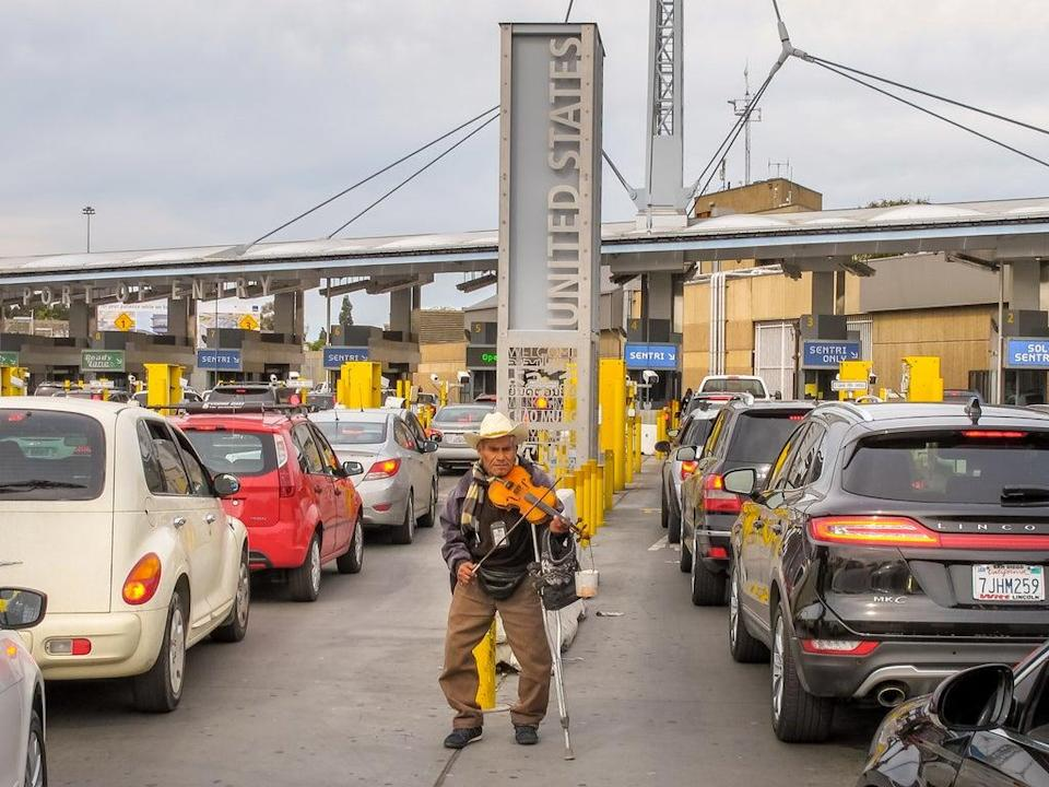 An elderly person plays his violin among the dozens of cars queued on the Mexican side waiting to cross the border between Mexico and the United States, at the border station between Tijuana and San Ysidro. (Getty Images)
