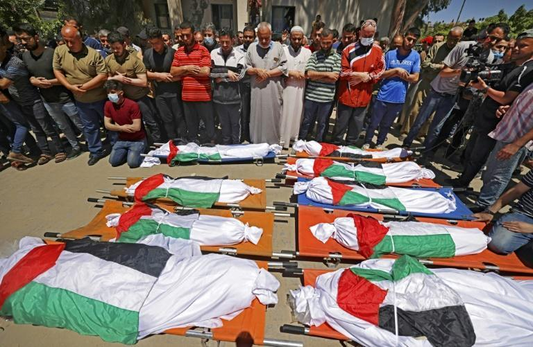 Palestinians in Gaza City pray during the funeral of a family of 10 who were killed in an Israeli air strike on the western Gaza Strip in May