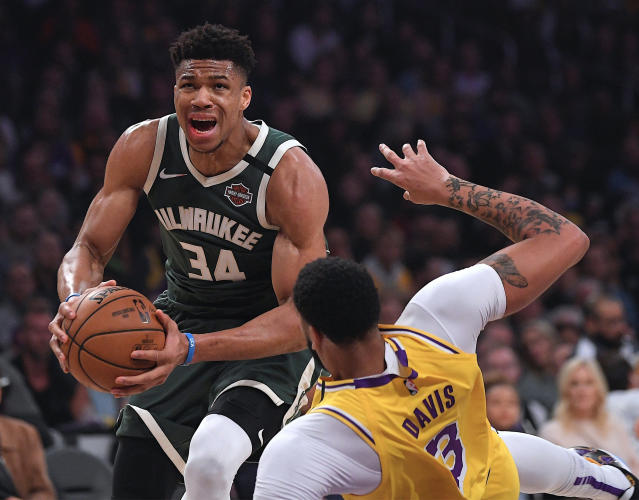 FILE - In this March 6, 2020, file photo, Milwaukee Bucks forward Giannis Antetokounmpo (34) knocks down Los Angeles Lakers forward Anthony Davis as he drives to the basket during the first half of an NBA basketball game in Los Angeles. One of Antetokounmpos brothers says the Bucks stars social media was hacked, causing a series of bizarre and offensive tweets to come from that account. The Bucks and Octagon, the agency that represents the reigning MVP, confirmed the hacking. (AP Photo/Mark J. Terrill, File)