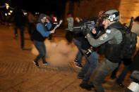 Israeli police officer stands in position as a stun grenade explodes by the gate to Jerusalem's Old City