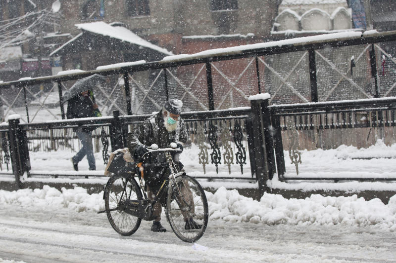 An elderly Kashmiri man pushes his cycle on a snow covered road in Srinagar, Indian controlled Kashmir, Thursday, Feb. 7, 2019. The fresh snowfall has resulted in disruption of air and road traffic for the second consecutive day between Srinagar and Jammu, the summer and winter capitals of India's troubled state. (AP Photo/ Dar Yasin)