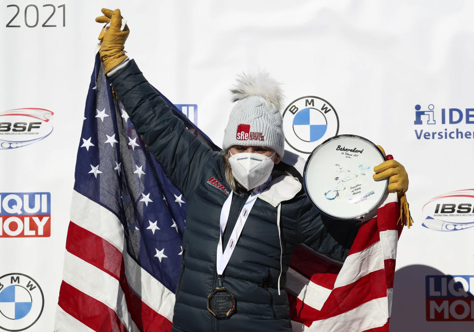 Bobsleigh pilot Kaillie Humphries of the United States holds the trophy for the new track record as she celebrates on the podium after taking first place in the women's monobob race at the Bobsleigh and Skeleton World Championships in Altenberg, Germany, Sunday, Feb.14, 2021. (AP Photo/Matthias Schrader)