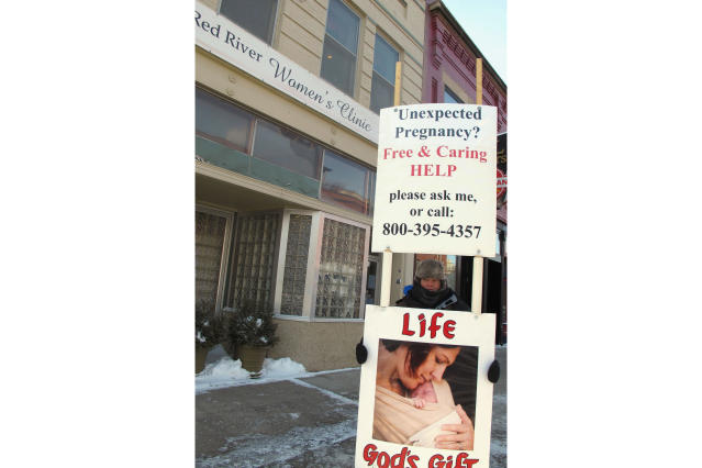 FILE - In this Feb. 20, 2013 file photo, an abortion protester stands outside the Red River Valley Women's Clinic in Fargo, N.D. North Dakota's sole abortion clinic filed a federal lawsuit Tuesday, June, 24, 2019, over two state laws it believes forces doctors to lie, including one measure passed this year requiring physicians to tell women that they may reverse a so-called medication abortion if they have second thoughts. The complaint from the Center for Reproductive Rights on behalf of the Red River Women's Clinic. (AP Photo/Dave Kolpack, File)