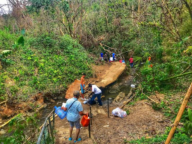 <p>People bath and collect water from a stream in Bayamon, Puerto Rico. (Photo: Caitlin Dickson/Yahoo News) </p>