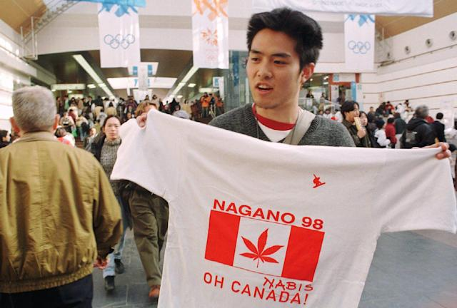A vendor in the Nagano train station hawks t-shirts showing a Canadian flag with a marijuana leaf substituted for a maple leaf in reference to Canadian snowboarder Ross Rebagliati. (AP Photo/Robert F. Bukatyt)