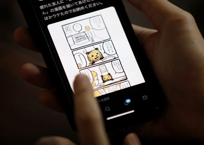 Japanese manga artist Kamentotsu shows his his four-panel strip comic 'Koguma's Cake Shop' on his smartphone at his workspace in Tokyo