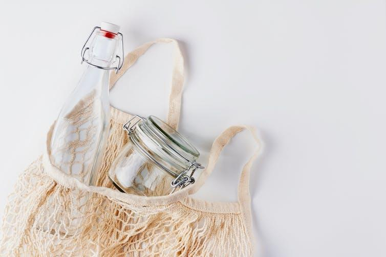 A fabric bag filled with a glass bottle and mason jar.