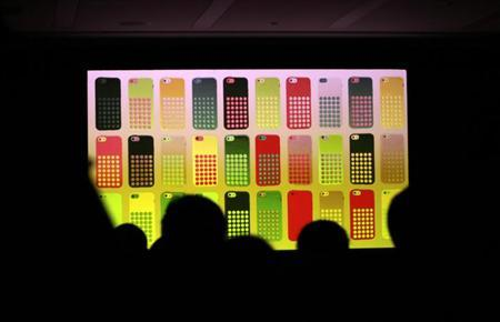 Journalists watch a screen showing the new iPhone 5C in different colours at Apple Inc's announcement event in Beijing, September 11, 2013.