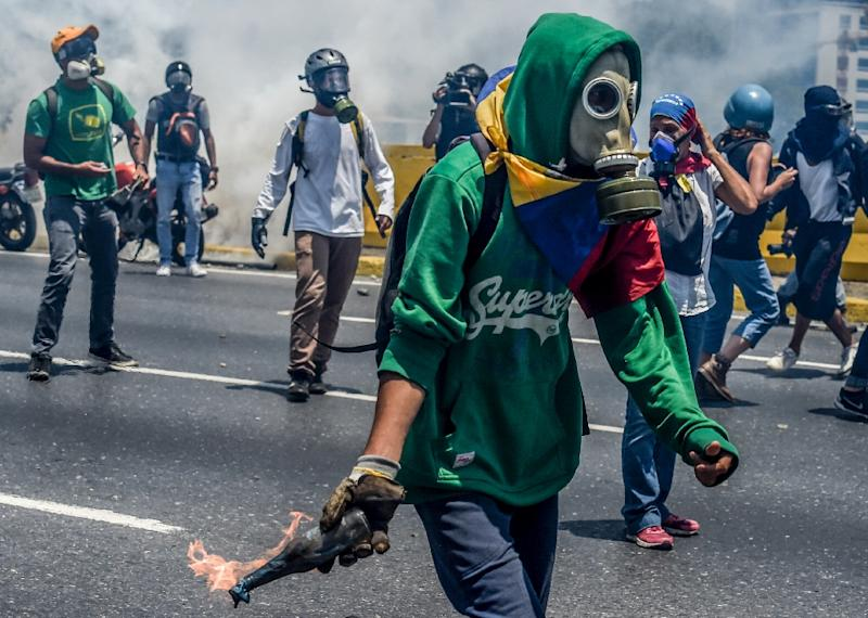 Venezuelan opposition activists clash with riot police during a protest march against President Nicolas Maduro in Caracas on April 26, 2017