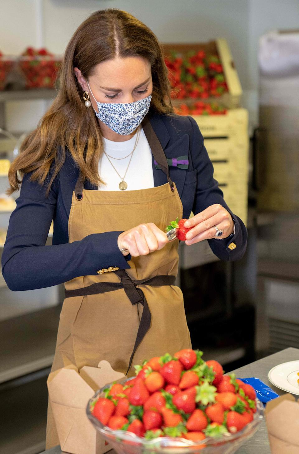 Britain's Catherine, Duchess of Cambridge, Patron of the All England Lawn Tennis Club, preparies strawberries in the Wingfield kitchen during her visit on the fifth day of the 2021 Wimbledon Championships at The All England Tennis Club in Wimbledon, southwest London, on July 2, 2021. - RESTRICTED TO EDITORIAL USE (Photo by AELTC/Thomas Lovelock / POOL / AFP) / RESTRICTED TO EDITORIAL USE (Photo by AELTC/THOMAS LOVELOCK/POOL/AFP via Getty Images)