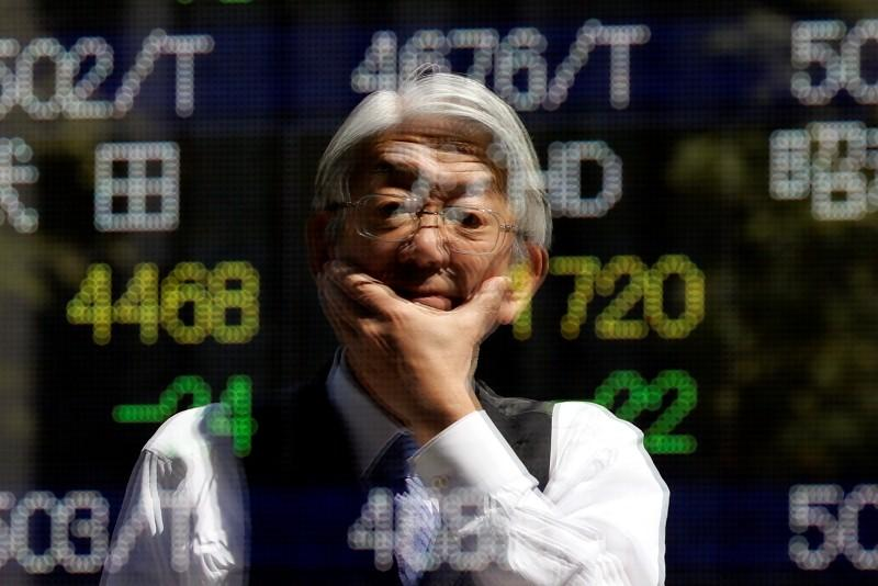 Man is reflected in an electronic stock quotation board outside a brokerage in Tokyo