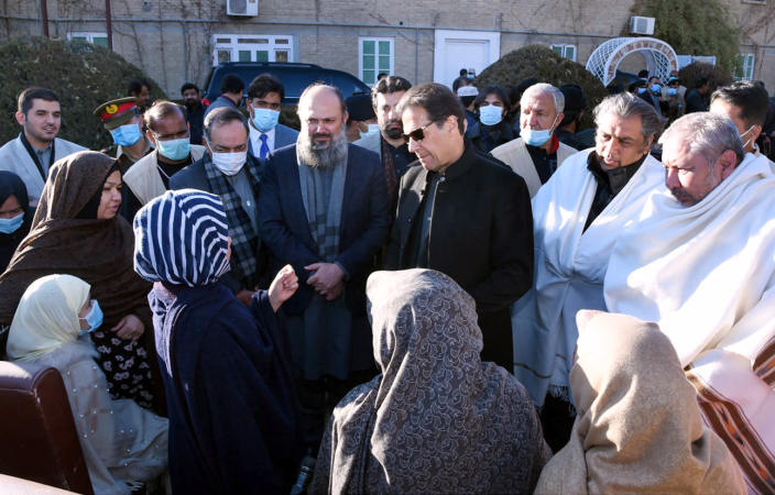 In this photo provided by Press Information Department, Pakistani Prime Minister Imran Khan, center, and other officials listen to families of the Shiite Hazara community's coal mine workers, who were killed by gunmen near the Machh coal field, at a meeting, in Quetta, Pakistan, Saturday, Jan. 9, 2021. Hundreds of Pakistani Shiites gathered to bury 11 coal miners from the minority Hazara community who were killed by the Islamic State group, ending over a week of protests that sought to highlight the minority community's plight. (Press Information Department via AP)